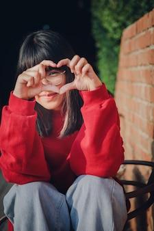 ハートのサインのように指を作る陽気なアジアのティーンエイジャーの肖像画