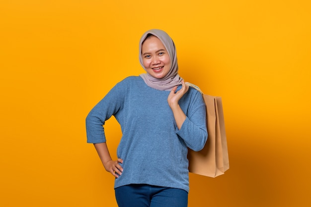 黄色の背景の上の買い物袋を保持している陽気なアジアの女性の肖像画