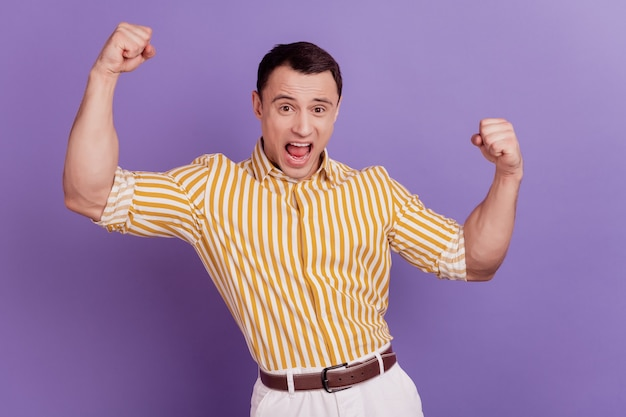 陽気なびっくりした男の肖像画は、紫色の背景に勝利の悲鳴を祝う拳を上げる