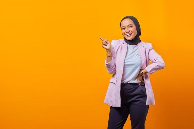 빈 공간에서 손가락을 가리키는 쾌활한 매력적인 아시아 여성의 초상화