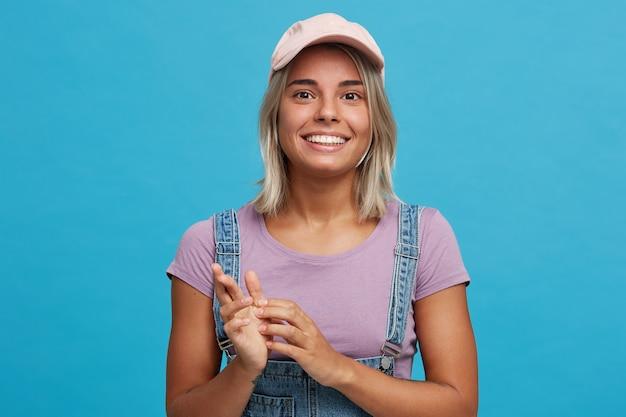 陽気な魅力的な金髪の若い女性の肖像画はピンクの帽子、紫のtシャツを着て、デニムのオーバーオールは青い壁に孤立して幸せと笑顔を感じます
