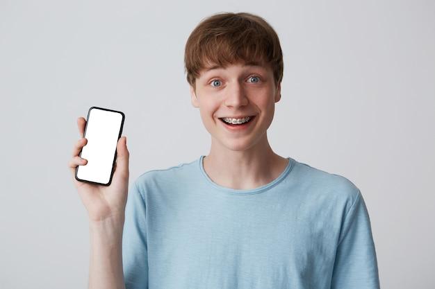 歯にブレースと陽気な魅力的な若い男の学生の肖像画は青いtシャツを着ています