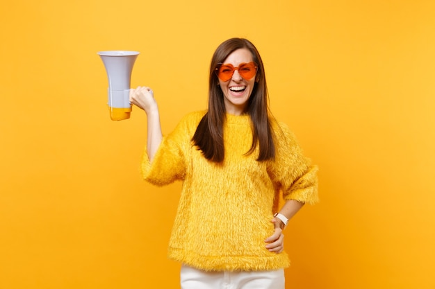 明るい黄色の背景に分離されたメガホンを保持している毛皮のセーターオレンジハート眼鏡で陽気な魅力的な若い女性の肖像画。人々の誠実な感情、ライフスタイルのコンセプト。広告エリア。