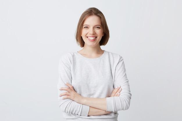 Портрет веселой привлекательной молодой женщины в лонгсливе, стоящей со скрещенными руками и улыбающейся
