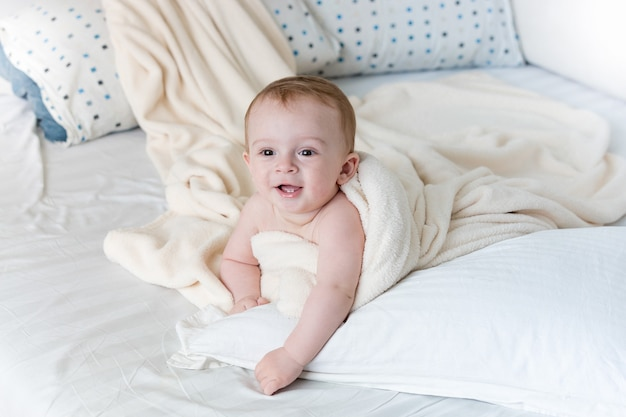 흰 담요 아래에 큰 베개에 누워 쾌활한 아기의 초상화