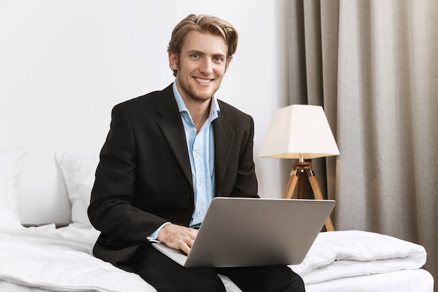 Портрет веселый бородатый директор компании в стильном черном костюме, ярко улыбаясь, работает на ноутбуке в уютном гостиничном номере во время деловой поездки.
