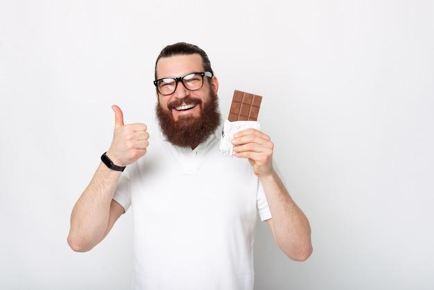 Портрет веселого бородатого мужчины в белой футболке показывает палец вверх и плитку шоколада