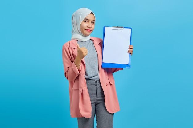 青い背景に親指を示すクリップボードを保持している陽気な美しいアジアの女性の肖像画