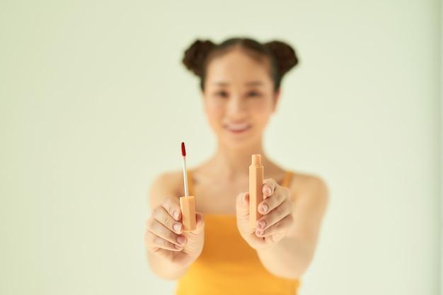 明るい背景の上に口紅を示す陽気な美しいアジアの女性の肖像画。