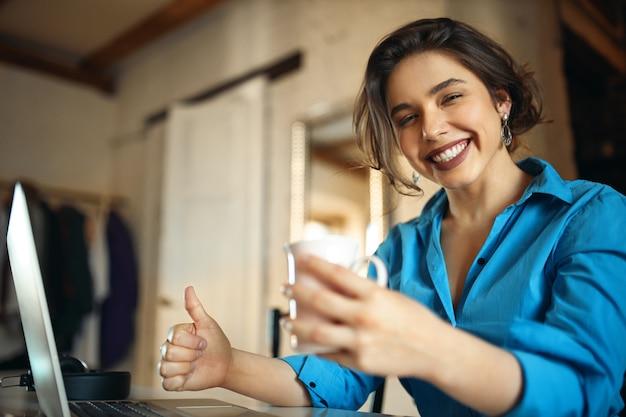 Портрет веселой красивой студентки в синем платье, широко улыбаясь, весело проводя время в интернете на ноутбуке Бесплатные Фотографии