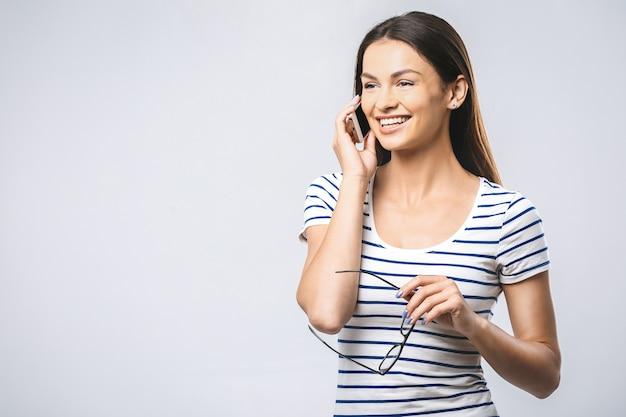 笑顔の携帯電話を使用して陽気な美しい若い女性の肖像画