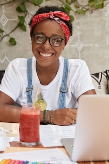 陽気な黒人学生の肖像画は居心地の良いコーヒーショップで宿題をします