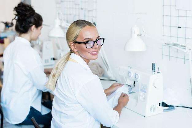 Портрет веселой блондинки в очках, сидящей за швейной машиной в заводском магазине