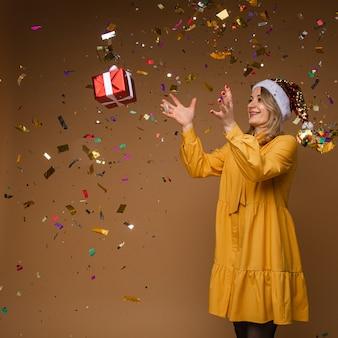 반짝이 산타 모자와 노란 드레스를 던지고 밝은 금발 백인 여자의 초상화 떨어지는 색종이와 크리스마스 선물 포장