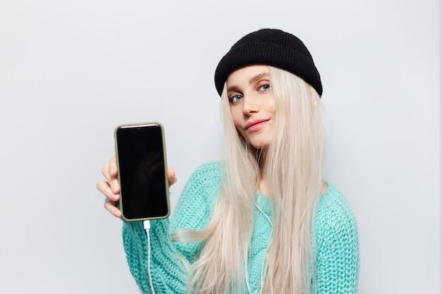 スマートフォンを手に陽気なブロンドの女の子の肖像画