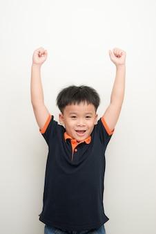 孤立した白い背景の上に手を上げた陽気な少年の肖像画
