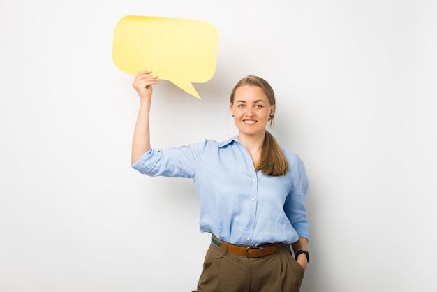 Портрет жизнерадостной деловой женщины в синей рубашке с желтым пустым речевым пузырем
