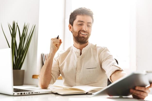Портрет веселого бизнесмена 30-х годов в белой рубашке, работающего с ноутбуком и бумажными документами, сидя в ярком офисе