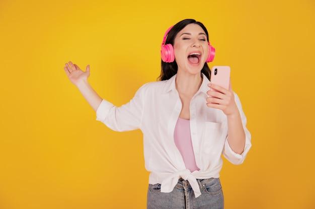 Портрет веселой беззаботной девушки держит телефон носить наушники поет на желтом фоне