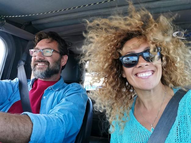 休暇中に車でロードトリップを楽しんでいる陽気な白人カップルの肖像画。車に座って休暇の旅を楽しんでいる興奮したカップル