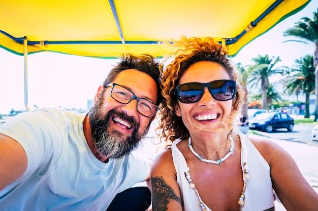 도로 여행 중 휴가를 즐기는 쾌활한 백인 부부의 초상화. 그들의 여행 동안 웃 고 행복 한 커플입니다. 휴가에 셀카를 찍는 즐거운 커플