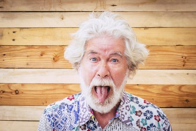 木の背景を持つ陽気な白人シニアクレイジー男の肖像画-面白い表現の代替と若い老人-多様性の概念と年齢のための白い髪とひげ-若々しいライフスタイル