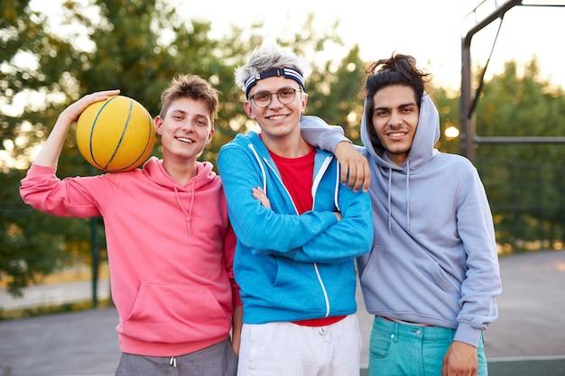 Портрет веселых кавказских мальчиков-подростков на баскетбольной площадке