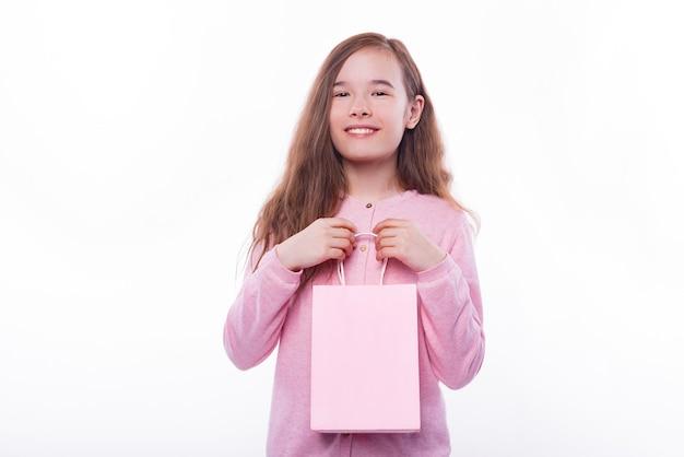 분홍색 쇼핑백을 들고 밝은 아이 여자의 초상화