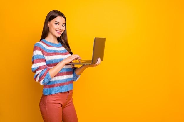 Портрет веселой уверенной девушки, держащей в руках ноутбук
