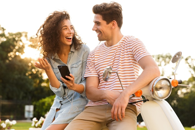 쾌활한 부부의 초상화, 도시 거리에 함께 오토바이에 앉아있는 동안 음악을 듣고 이어폰을 착용