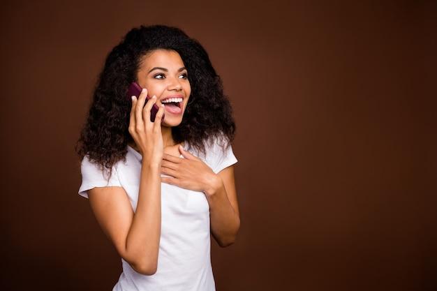 陽気なクレイジー面白いアフロアメリカ人の女の子の肖像画は彼女の友人とスマートフォンの話を使用して信じられないほどの販売情報を共有する白いtシャツを着ています。