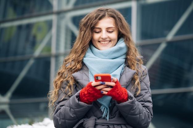 Портрет веселой кудрявой молодой женщины текстовых сообщений на смартфоне, стоя на улице в зимнем городе на новый год.