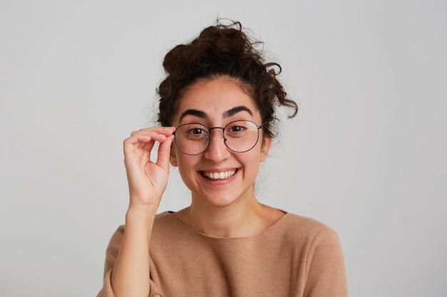 巻き毛の陽気なかわいいグルジアの若い女性の肖像画はベージュのプルオーバーを着用し、白い壁に隔離されて幸せと笑いを感じます