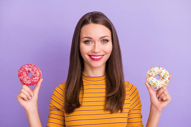 Портрет веселой милой милой милой девушки, держащей два пончика, наслаждается закусками быстрого питания, носит свитер повседневного стиля, изолированный на фиолетовом цвете