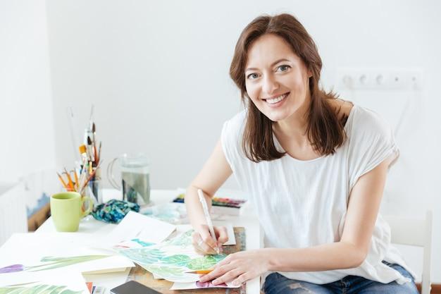 Портрет веселой милой женщины-художника, сидящего и рисующего в мастерской