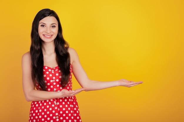 Портрет веселой милой женщины руки демонстрируют пустое пространство носить точечное красное платье на желтом фоне