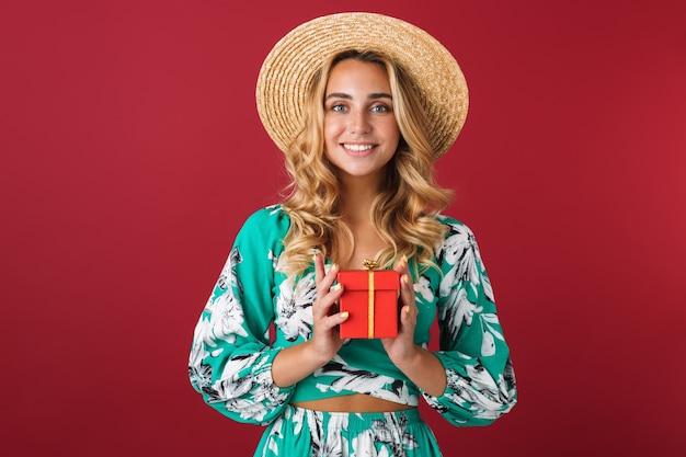 Портрет веселой милой молодой блондинки в ярко-синем платье позирует изолированным над красной стеной, держащей настоящую коробку.