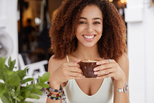 덥수룩 한 아프리카 haistyle을 가진 쾌활한 어두운 피부 여성의 초상화, 커피 또는 라떼 한잔 보유, 좋은 분위기에있는 카페테리아 내부에 앉아 있음