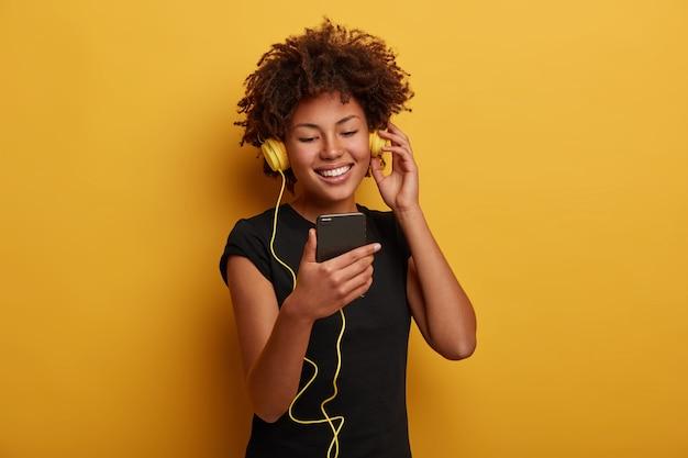곱슬 헤어 스타일을 가진 쾌활한 정력적 인 여자의 초상화, 재미있는 비디오를보고, 노란색 배경 위에 절연 스마트 폰에 연결된 헤드셋을 착용