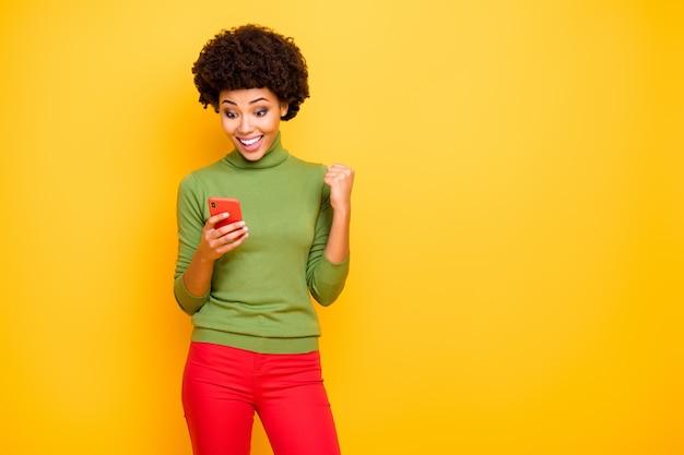 陽気な興奮した治療法の肖像画は、歯を見せる赤いズボンで彼女の電話で新しい通知を読んでいるかなり素敵な大喜びの女の子です。