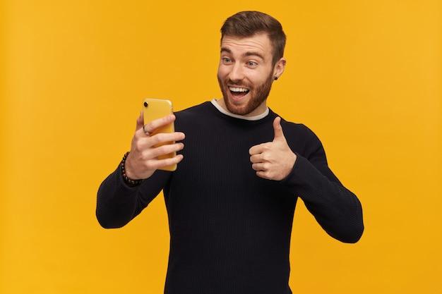 갈색 머리와 수염을 가진 쾌활하고 흥분된 남자의 초상화. 피어싱이 있습니다. 검은 스웨터를 입고. 영상 채팅이 있습니다. 셀카를 만들고 엄지 손가락을 표시합니다. 노란색 벽 위에 절연 스탠드