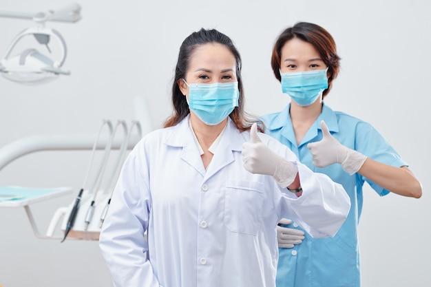 보호용 마스크와 실리콘 장갑을 끼고 엄지손가락을 치켜들고 카메라를 바라보는 쾌활한 경험 많은 치과의사와 간호사의 초상화