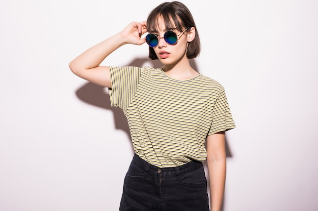 Портрет веселой модной хипстерской девушки в солнцезащитных очках, изолированной повседневной одежде