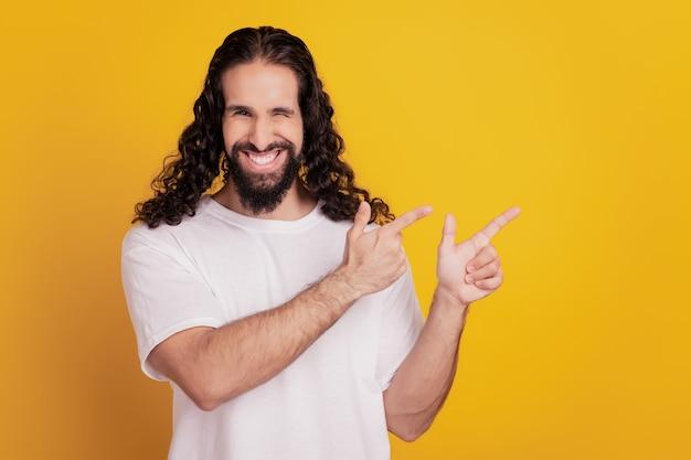 黄色の背景に陽気な軽薄な魅力的な男の直接人差し指の空白の肖像画