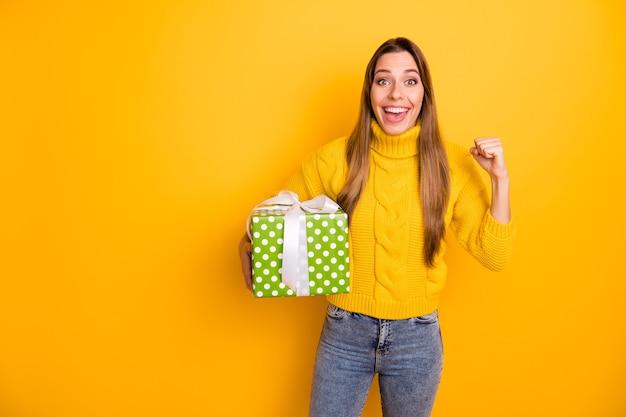 Портрет веселой веселой девушки празднуют получить зеленую пунктирную подарочную коробку, которую она выиграла в лотерею, крик, вау, боже, поднять кулаки, носить вязаный воротник-джемпер, изолированную желтую стену