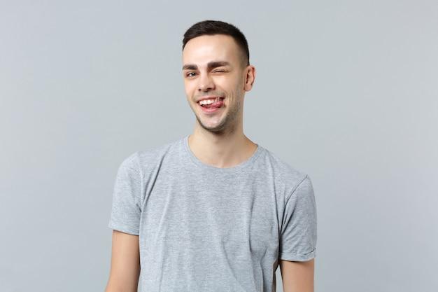 舌を示すカジュアルな服を着て陽気な面白いまばたき若い男の肖像画
