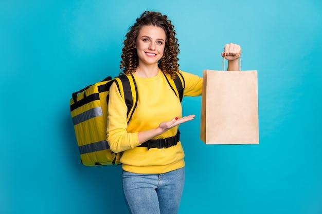 Портрет веселой девушки приносит сумку с обедом на вынос, изолированную на синем фоне