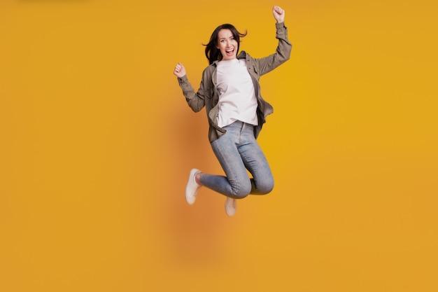黄色の背景に分離された上げられた握りこぶしで陽気な女の子のジャンプの肖像画