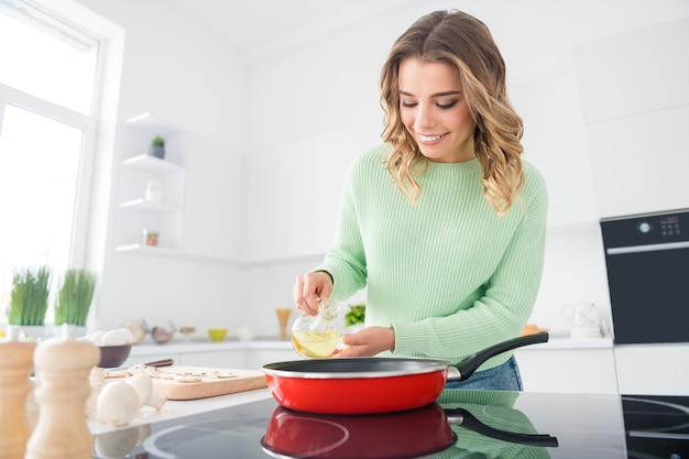 油を注ぐおいしいおいしい家庭料理を準備する陽気な女の子の肖像画