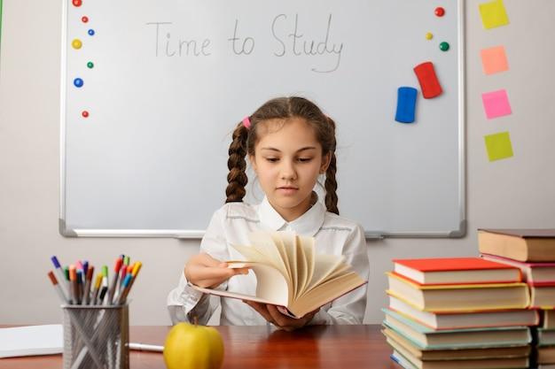 읽을 텍스트를 선택하는 책을 통해 찾고 쾌활한 여자 학교 학습자의 초상화
